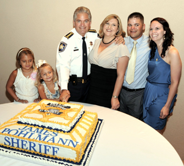 The sheriff cuts the cake at the reception following the swearing-in. With him are daughters Victoria and Olivia, wife, Monique, son Justin and Justin's fiancée Alison Ancalade.