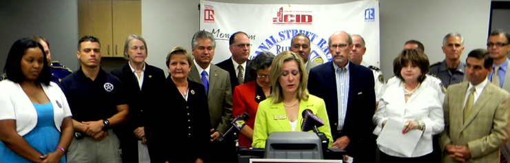 Darlene Cusanza, President and CEO of Crimestoppers Inc. which offers rewards for tips to solve crimes, announces a Sept. 22 foot race on Canal Street to help the group raise $50,000 to make up funding cuts. Behind her are numerous law enforcement officials, including Sheriff James Pohlmann, who support the effort, as well as New Orleans city officials, a crime victim's mother and representatives of the Saints and from the New Orleans Metropolitan Association of Realtors which has donated $10,500 to cover costs of the race.