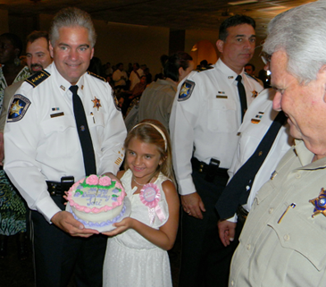 The sheriff's daughter, Victoria, celebrates her 8th birthday with a cake at the reception  after her father is sworn in.