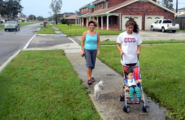 "When the sun came out Thursday, Sonia Gavarrete of Chalmette, in the background, came out to take a walk along Jean Lafitte Parkway with Erica Alfaro, who is pushing the stroller carrying baby Christina Fernandez. With them is their dog, Trixie.  ""We've been in the house two days. It's great to see the sun come out,'' said Gavarrete."