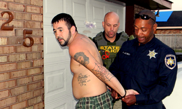 Sheriff's Office Cpt. Richard Jackson applies handcuffs to suspect David  Bennett, wanted for crack cocaine distribution, outside the door of Bennett's residence in the drug round-up conducted Thursday by the St. Bernard Sheriff's Office. Also shown is State Police Sgt. Jody Hasselback.
