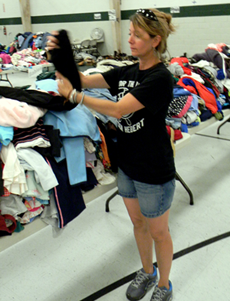 Suzanne Shaffer looks over donated clothes at Lynn Oaks School, where she discovered a burglary of  $15,000 of goods on Sunday.