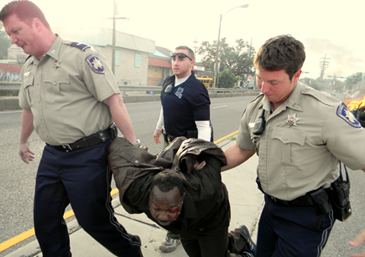 Suspect Cyprian Robertson, 37, of Chalmette, is carried away from his burning auto by by, at left, St. Bernard Sheriff's Deputy Lt. Raymond Whitfield, Louisiana Probation and Parole Agent Andrew Bodine and Deputy Jonathan Smith after Robertson fled a  Chalmette courtroom while deciding whether to accept a deal in a criminal case, then crashed and burned a car on the Industrial Canal bridge ramp in New Orleans.