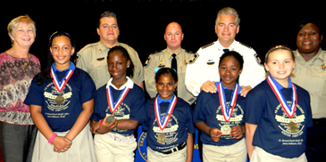 At Chalmette Elementary School, essay winners were, in front, Kalvionna Washington, Jy'Jay Johnson, A'Jada Hagan, Paijanee Metz, Emily Cauthern.  In back are Princippal Elizabeth Winslow, Sgt. Darrin Miller, Capt, Ronnie Martin, Sheriff James Pohlmann and Lt. Lisa Jackson.