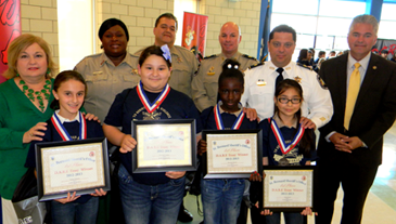 Winners of the D.A.R.E. essays at Arabi Elementary are, in front row: Taylor Hebert, Dawnell Conley, Kennise Baker and Katie Jovel. In the back are Principal Carla Carolla, Lt. Lisa Jackson, Sgt. Darrin Miller, Capt. Ronnie Martin, Maj. Chad Clark and Sheriff  James Pohlmann.