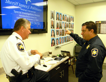 Sheriff James Pohlman and Maj. Chad Clark discuss the drug round-up before addressing assembled officers who will participate. In background are photos of the suspects to be arrested.