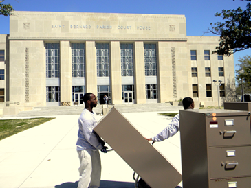 Employees of a moving company unload office files to bring into the St. Bernard Parish Courthouse, which reopens Monday.