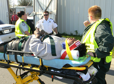 Torraino Johnson is shown on a gurney with emrgency medical technicians Robyn Penick, left, and April Wensel, right, both of Acadian Amlulance Srvices, who are about to take him to an ambulance. In the background is Maj. Robert McNab, head of the Criminal Investigations Bureau of the Sheriff's Office.