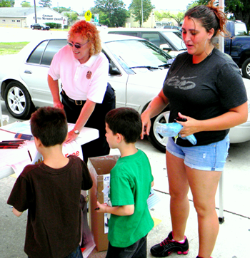 Two youngsters pick out pencils, key chains, coloring books and other items the Sheriff's Office gave out to children during the drug take-back effort.
