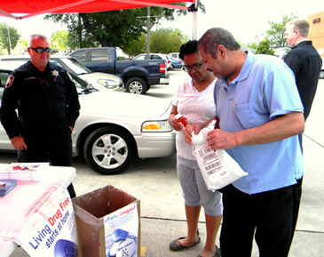A couple gets rid of their old medications. At left is Sgt. Joey Alfonso and at right is Bill Hagoort , district manager for Walgreen.