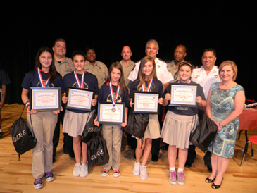 D.A.R.E. essay winners at Lacoste Elementary were Angela Romero-Barron, Kieran Marshall, Taylor Meyer, Logan Dusang and Victoria Pecunia and with them are Lacoste Principal Stacie Alfonso. In the back row are D.A.R.E. instructors Sgt. Darrin Miller, Lt. Lisa Jackson and Capt. Ronnie Martin, Sheriff James Pohlmann, Lt. Richard Jackson and Maj. Chad Clark.