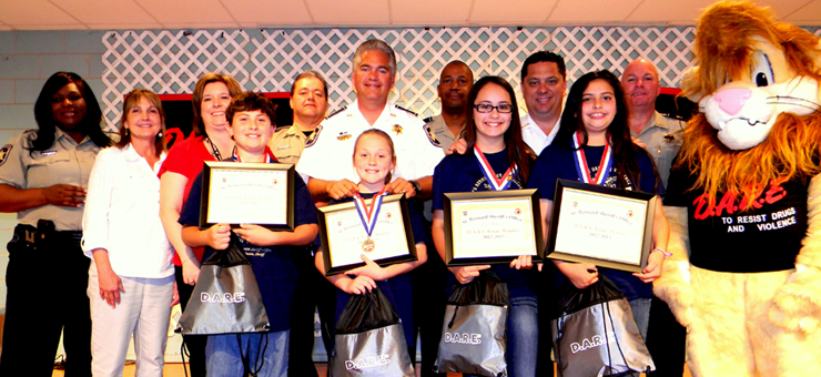 At Our Lady of prompt Succor School, from left are Lt. Lisa Jackson, teachers Anne Fabian and Rachel Vogt, 2nd place D.A.R.E. essay winners Joey Bazile and Katie Mahler; first place essay winners Emily Zepeda and Kelsey Juan, Sgt. Darrin Miller, Sheriff James Pohlmann, Lt. Richard Jackson, Maj. Chad Clark, Capt. Ronnie Martin and mascot Daren the Lion, portrayed by Cpl. Jessica Gernados.