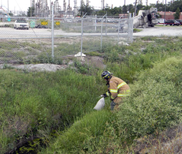 A St. Bernard firefighter places sandbags in the ditch as a precaution in case its water was contaminated by the leaking chemical from the truck, which can be seen in the background.