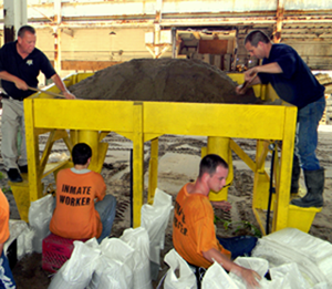 Sheriff's Dep. Brian Cadzow, left, helps trusty prisoners make sandbags in preparation for hurricane season.