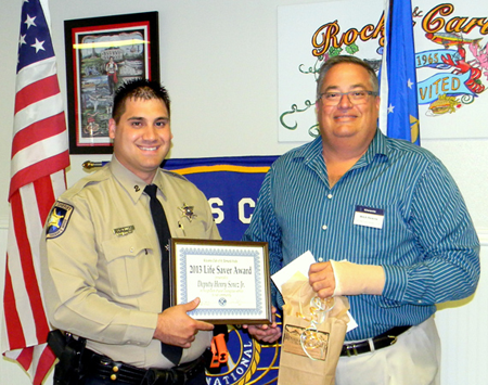 Dep. Sheriff Henry Senez Jr. is presented the St. Bernard Kiwanis Club Life-Saver Award by Mitch Perkins of the club.