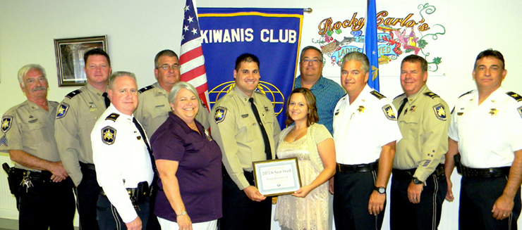 Dep. Henry Senez Jr. holds the Kiwanis Life-Saver Award with his wife, Melissa, to his left, and they are surrounded by sheriff's deputies and club officials. From left in the front row are Maj. Adolph Kreger, Kiwanis member Shirley Pechon, Senez and wife, Sheriff James Pohlmann, Capt. C.J. Arcement and Col. John Doran. In back, from left, are Sgt. Dick Beebe, Lt. Ray Whitfield, Lt. Robert Broadhead and Kiwanis member Mitch Perkins.