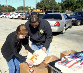 Carolyn Kimball of Meraux and Maj. Chad Clark empty a bag of medicatioms she brought into a collection box.