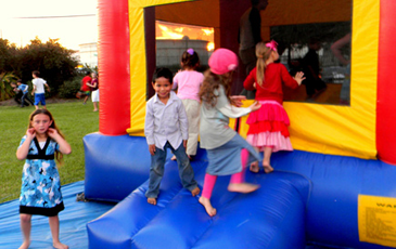 Children prepare to enter a bounce tent at a party in Chalmette.