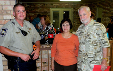 Sheriff's Deputy Jules Henry with Carol and Al Beaubouef at their party in the Lexington Place subdivision in Meraux.