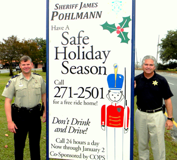 Signs telling the public about the free Holiday Ride Home program have been put up around St. Bernard. Shown at one is Sheriff James Pohlmann, at right, with Lt. Brent Bourgeois of the Traffic Division.