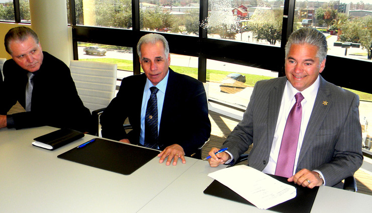 Sheriff Pohlmann, right, is shown after signing the documents. To his right is Pete Tufaro, in charge of the Sheriff's Office building projects, and at left is Chief Deputy Sheriff Richard Baumy.
