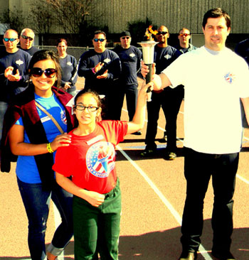 Alexis Hernandez, 12, of Arabi Elementary, center, holds the Special Olympics torch aloft with the help of Gerald Neyland of Arabi, with her older sister Elizabeth Hernandez, at left and a group of St. Bernard Parish sheriff's deputies behind them as they get ready to march in the opening ceremony of the school system's Special Olympics games held March 14 at Chalmette High's football stadium. Alexis, a eunner, will compte in the national Special Olympics in June at Princeton, N.J.