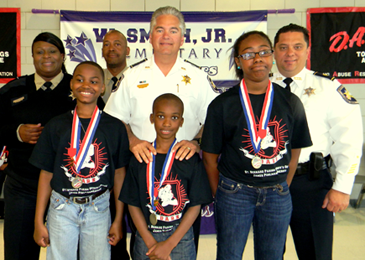 D.A.R.E. contest winners at Willie Smith Jr. Elementary were, from left, Jaydon Green, Kiron Hill and LaShawn Williams. Behind them are D.A.R.E. program head Lt. Lisa Jackson, Lt. Richard Jackson, Sheriff James Pohlmann and Maj. Chad Clark. Essay runner-ups, not shown, were Coree Green, Kewayne Lafrance and E'sinenei Barthelemy.
