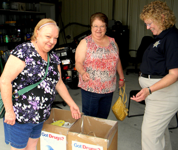 Linda Ricks, left, and Susan Comeaux turn in old medications to Capt. Pat Childress at the drug take-back event.