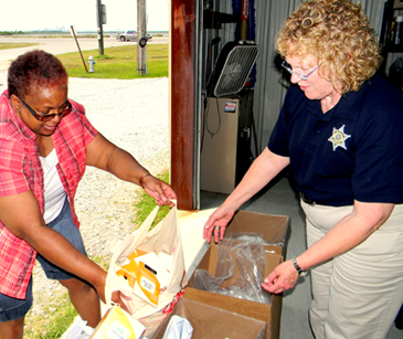 Donnetta Smith of New Orleans places a large amout of old prescription medication in a bin as Capt Pat Childress helps her at the drug take-back event held April 26 at the sheriff's Paris Road station