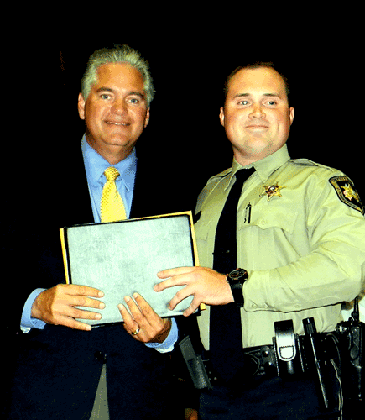 Dep. Robert Maloz receives his certificate from Sheriff Pohlmann.