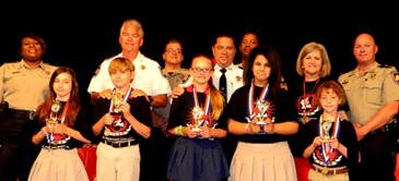 Winners of the 5th grade D.A.R.E. essay contest at Lacoste Elementary were: in front from left, Jaidyn Cone, Tyler Gremillion, Kayleigh Richardson, Yasmine Gaber and Hallie Miller. In back, from left, are Lt. Lisa Jackson, who heads the D.A.R.E. program; Sheriff James Pohlmann, instructor Sgt. Darrin Miller, Maj. Chad Clark, Lt. Richard Jackson, 5th-grade teacher Dina Martinez and Capt. Ronnie Martin.