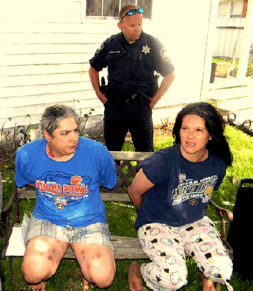 "Brandy Prosper, right, and Calogero Carbello, who lives with her in Chalmette, are handcuffed and sit on a bench in front of their residence after their arrests at their home on Wednesday, May 21. Behind them is Lt. Clifford ""Chip"" Englande of the Sheriff's Office. She is booked with heroin distribution and both are booked with possession of heroin and drug paraphernalia."