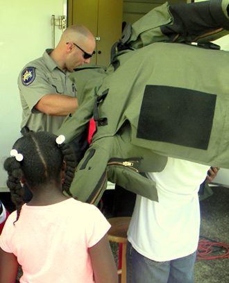 Sgt. Chris Scheeler of the Sheriff's Office bomb squad, shows youngsters how heavy a bomb suit is