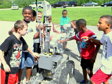 Participants in the Christian Fellowship summer camp surround the Sheriff's Office bomb robot, used to check out suspicious items, during a law enforcement day at the camp.