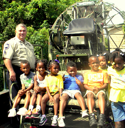 Dep. Shane Lulei with children aboard the Sheriff's Office airboat.