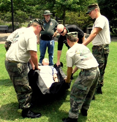 Participants in the Teen CERT camp use a mannequin to practice moving an injured person without further injury.