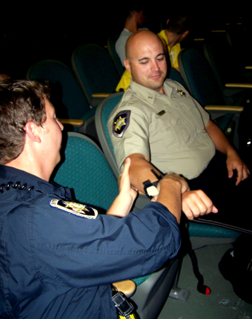 Sheriff's Deputy Jonathan Smith applies a tourniquet to an arm of Dep. Brad Nuccio