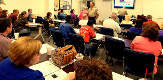 Capt. Charles Borchers in front of a large audience of participants at the Citizens Police Academy class.