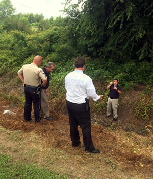 St. Bernard Parish sheriff's detectives and deputies look at the area where a man's body had just been removed from a ditch on the west side of Paris Road at Agriculture Road in Chalmette on Thursday afternoon. An autopsy will be done to determine cause of death.