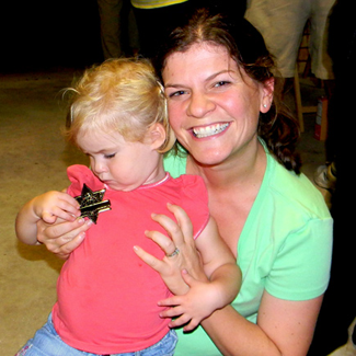 Emily Hanson holds her daughter, Elizabeth. who is looking down at her Junior Deputy badge she had just received at a National Night Out Against Crime party in Meraux in October 2013.
