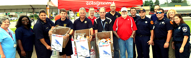 Sheriff James Pohlmann, Walgreens store manager Charles Mengel and several parish firefighters hold up boxes of prescription drugs turned in by the public at a drug take-back day held at Walgreens on Saturday, Sept. 27. Other Wa;greens emp;pyees, sheriff's depties and firefighters surround them.
