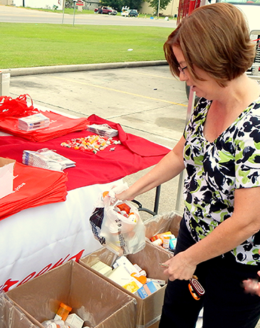 Sharie Waguespack of Chalmette drops medications in a box at the take-back event.