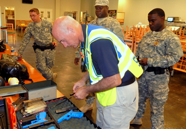 Lt. Raymond Theriot, deputy director of training for the St. Bernard Sheriff's Office, helps Guardsmen with weapons safety checks for the active shooter simulation drill.