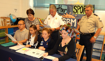 Sheriff James Pohlmann participated with St. Bernard Middle School students on Wednesday in the national student pledge against gun violence. Taking part in a live message shown to all homerooms in the school are, from left in front, school counselor Paul Tran, 8th-grade students Madison Melerine and Brissa Taylor and Assistant Principal Angela Seibert, who was also participating in Crazy Hair Week at the school. In back are Principal Sue Deffes, Sheriff Pohlmann and Lt. Robert Broadhead.