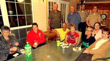 A Night Out Against Crime event at the home of Rosemary Gioe. seated at the top center of the table, in Chalmette. Detective deputies Lt. Richard Mendel and Ryan Melerine. shown in back, were assigned to the event.