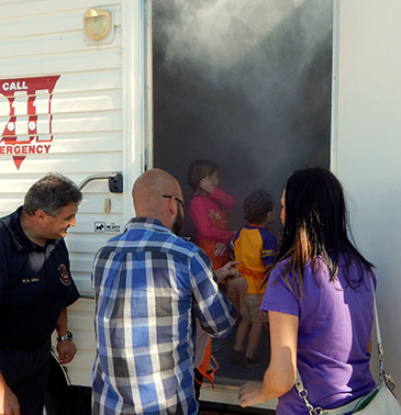 Smoke pours from the open door of the Fire Department mobile safety house as a family enters as Fire Dept. Capt. Rory Miller stands at left. The house is used to teach children how to drop and roll during a fire to avoid smoke inhalation.