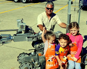 Sheriff James Pohlmann, with Olivia Cavalier, Noah Wagner and Isabelle Lulei, who are sitting on the sheriff's bomb robot, used to check out suspicious items to see if they contain an explosive.device.