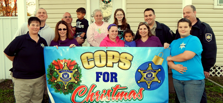 Shown after receiving a Thanksgiving dinner are the Boehm family and officers. From left are Lt. Jamie Penton, Dep. Jodi Mowers, Katie Boehm, her daughter Kamdyn, Dep. Darlene Ricks, Kaya Penton, daughter of Jamie Penton; in back row, from left, Dep. Wayne Babin Jr., Col. David Mowers holding Katie Boehm's son, Zachary; grandmother Sandra Boehm, Katie Boehm's daughter, Hanna; Cpl. Jeff Babin and Maj. Kevin Sensebe.