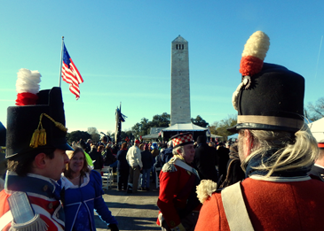 The Chalmette Monument is seen in the background as participants gather before the ceremony marking the 200th Anniversary of the Battle of New Orleans in Chalmette.