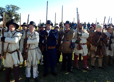 Costumed participants stand with their firearms during the ceremony.